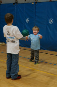 Photo of a small boy catching a ball from a volunteer