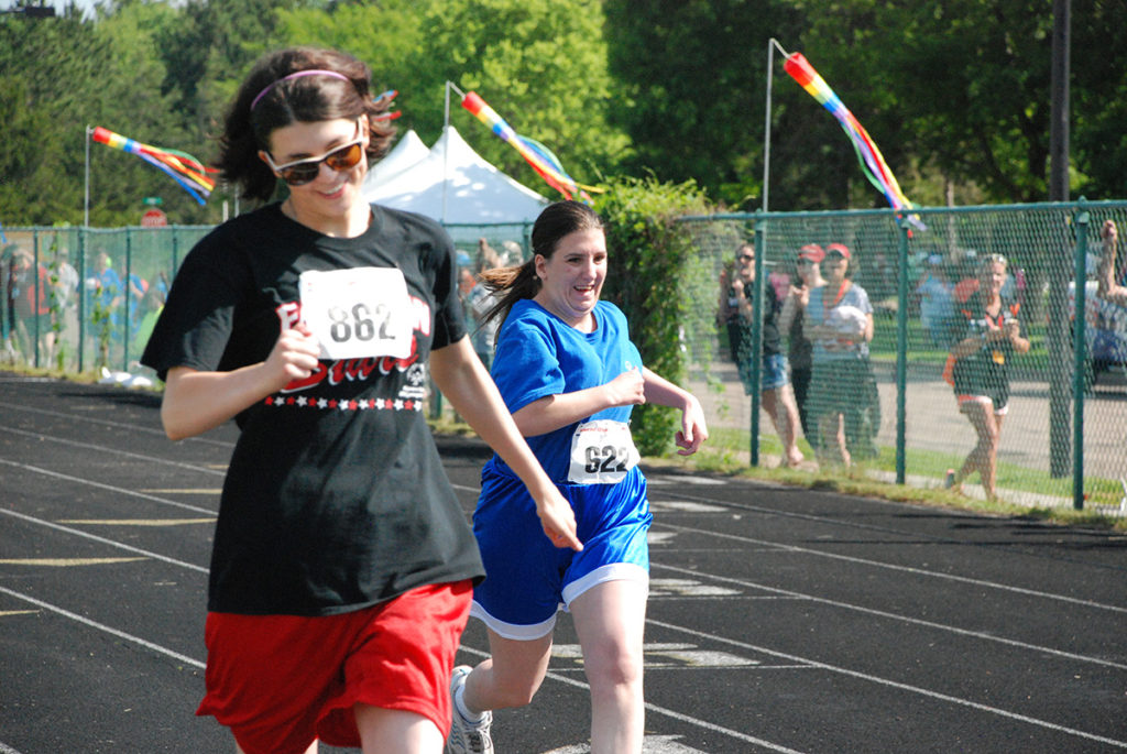 Photo of two women running on track